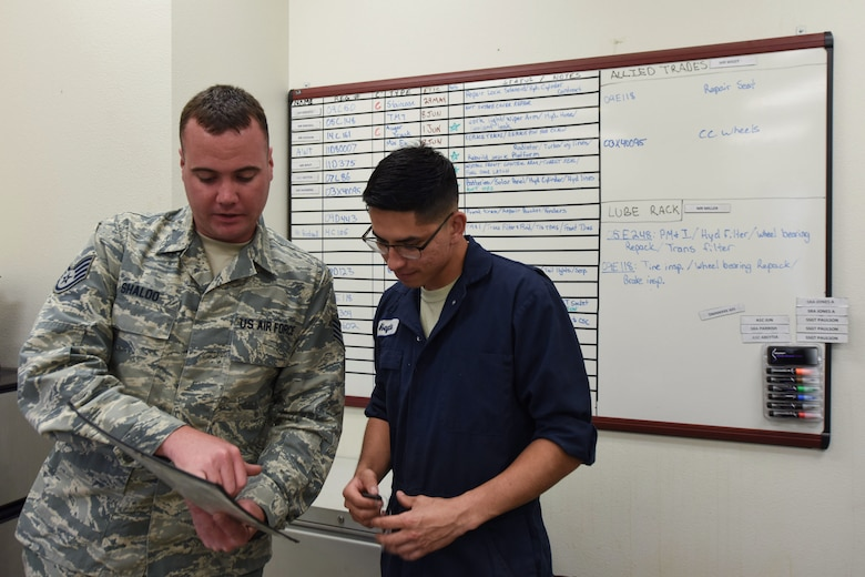 Staff Sgt. Kevin Shaloo, 30th Logistics Readiness Squadron NCO in charge of general purpose, tasks Airman 1st Class Jacobo Abeytia, 30th LRS vehicle maintenance apprentice, May 29, 2018, at Vandenberg Air Force Base, Calif. Shaloo was given a work order informing him of a customer needing a tire change. (U.S. Air Force photo by Airman Aubree Milks/Released)
