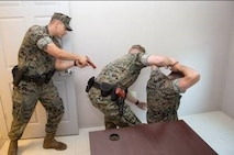 Military Police officers simulate arresting a suspect during the unsecured building sweep portion of their annual use of force training on Marine Corps Base Camp Lejeune, May 25.