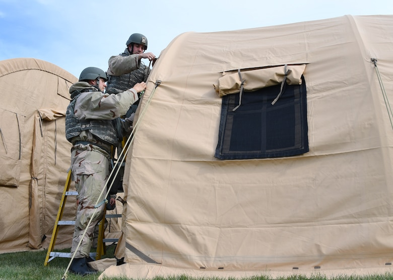 "Airmen with the 319th Civil Engineer Squadron work together to erect shelter systems as part of a training June 1, 2018, on Fargo Air National Guard Base, North Dakota. The training allowed the Airmen to hone their skills and prepare them to build ""tent cities"" as they might on deployments. The 319 CES participated in a three-day mission essential equipment training, which allowed multiple crafts within the squadron to practice their war-time efforts. (U.S. Air Force photo by Airman 1st Class Elora J. Martinez)"