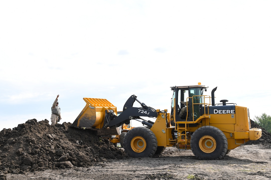 Staff Sgt. Newington Tamaalii, pavements and equipment supervisor with the 319th Civil Engineer Squadron, directs a front-end loader as part of mission essential equipment training June 1, 2018, on Fargo Air National Guard Base, North Dakota. Tamaalii and his team were practiced building a fuel bladder containment berm with the help of the 319 CES execution support team. (U.S. Air Force photo by Airman 1st Class Elora J. Martinez)