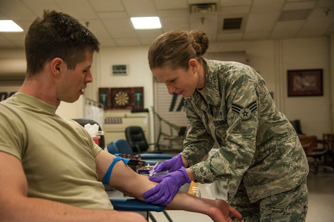 Senior Airman Rocquisha Locke inoculates Airman 1st Class Kadienne Simons during an Individual Medical Readiness activity May 24