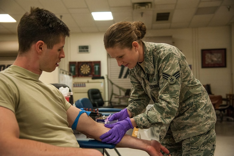 Senior Airman Rocquisha Locke inoculates Airman 1st Class Kadienne Simons during an Individual Medical Readiness activity May 24