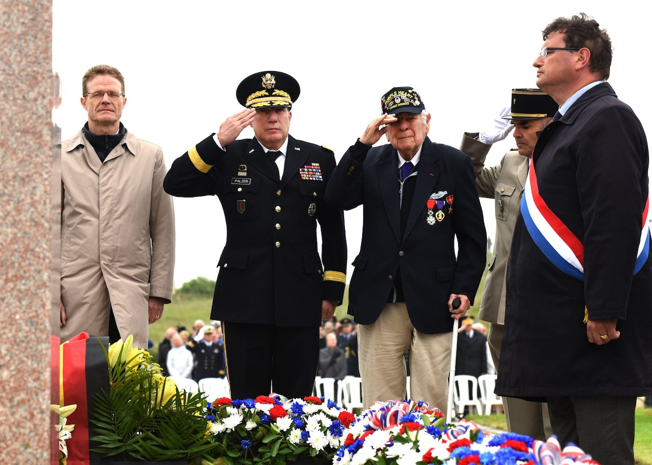 "D-Day veteran John Roman, center, and Army Maj. Gen. Mark W. Palzer, commander of the 79th Theater Sustainment Command, center left, salute for the playing of French and U.S. ""Taps"" during the Utah Beach Federal Monument Ceremony in Sainte-Marie-Du-Mont, France."