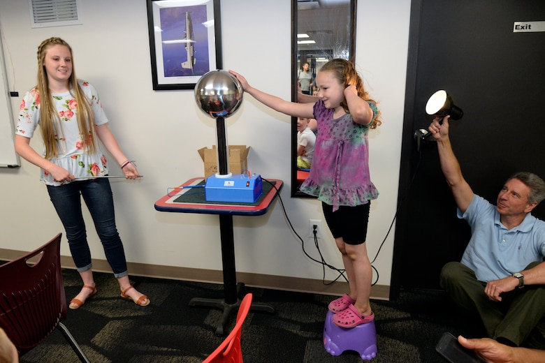 Rachel Griffin, a student summer intern at Hill Aerospace Museum, demonstrates electricity behavior to visitors with the help of Kier Thomas, June 5, 2018, at Hill Air Force Base, Utah. (U.S. Air Force photo by Todd Cromar)