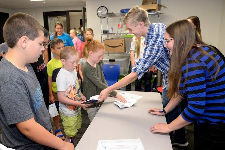 Raelyn Johnstun and Tim Trimble, student summer interns at the Hill Aerospace Museum, give children participating in the
