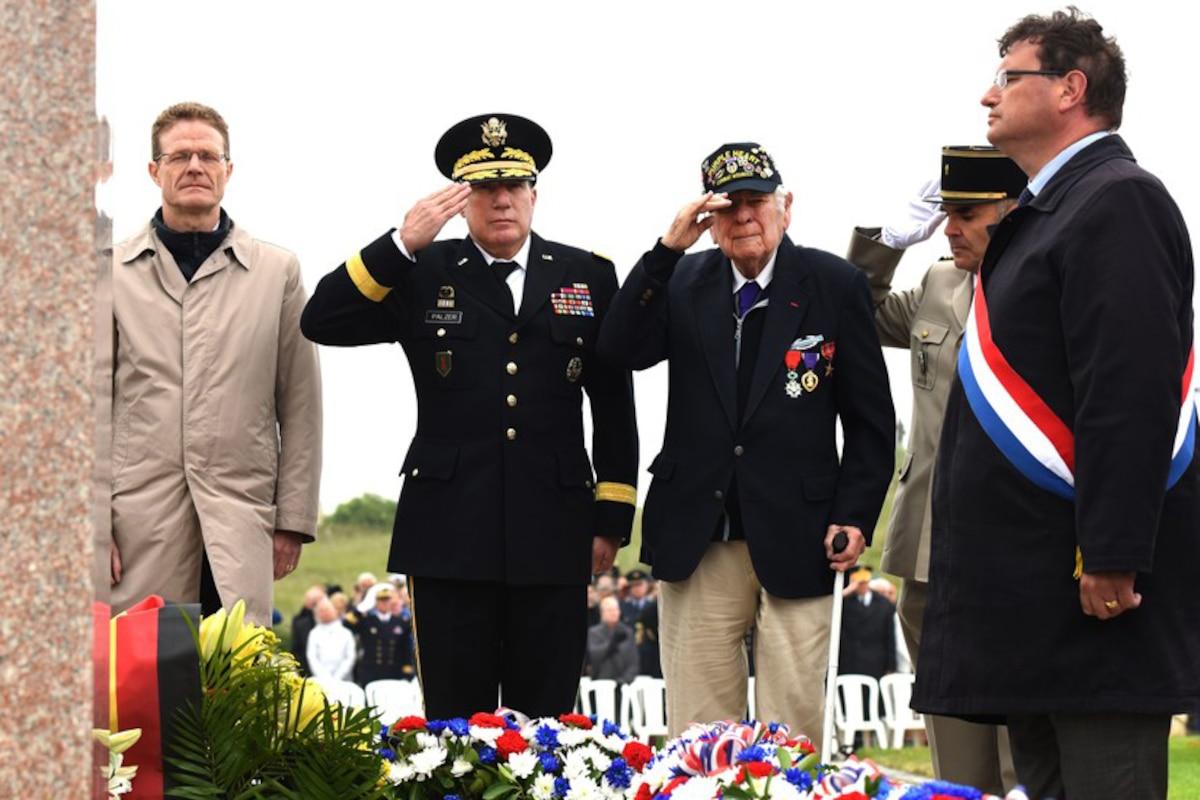 Service members and a veteran salute at a memorial.