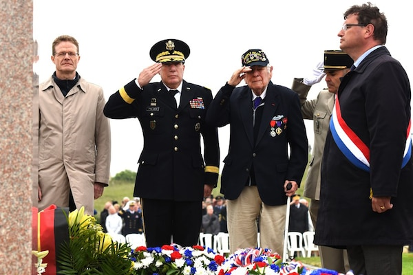 D-Day veteran John Roman, center, and Army Maj. Gen. Mark W. Palzer, commander of the 79th Theater Sustainment Command, center left, salute for the playing of French and U.S. taps during the Utah Beach Federal Monument Ceremony in Sainte-Marie-Du-Mont, France, June 6, 2018. DoD photo by Navy Chief Petty Officer Michael McNabb