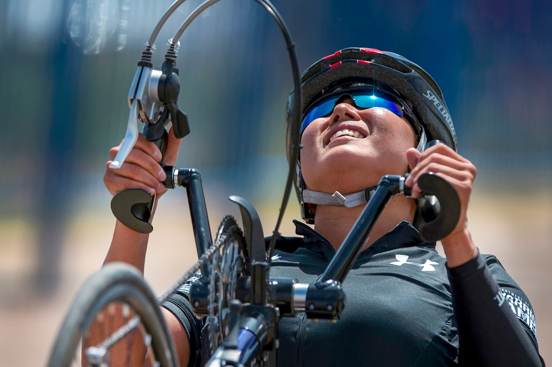 A soldier's face shows strain as she drives a handcycle up a hill.