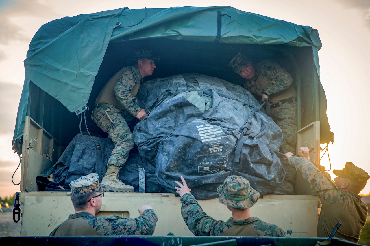 Marines in a truck pass tents to Marines outside a truck.
