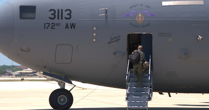 Air Force crewmember boards a C-17 aircraft.
