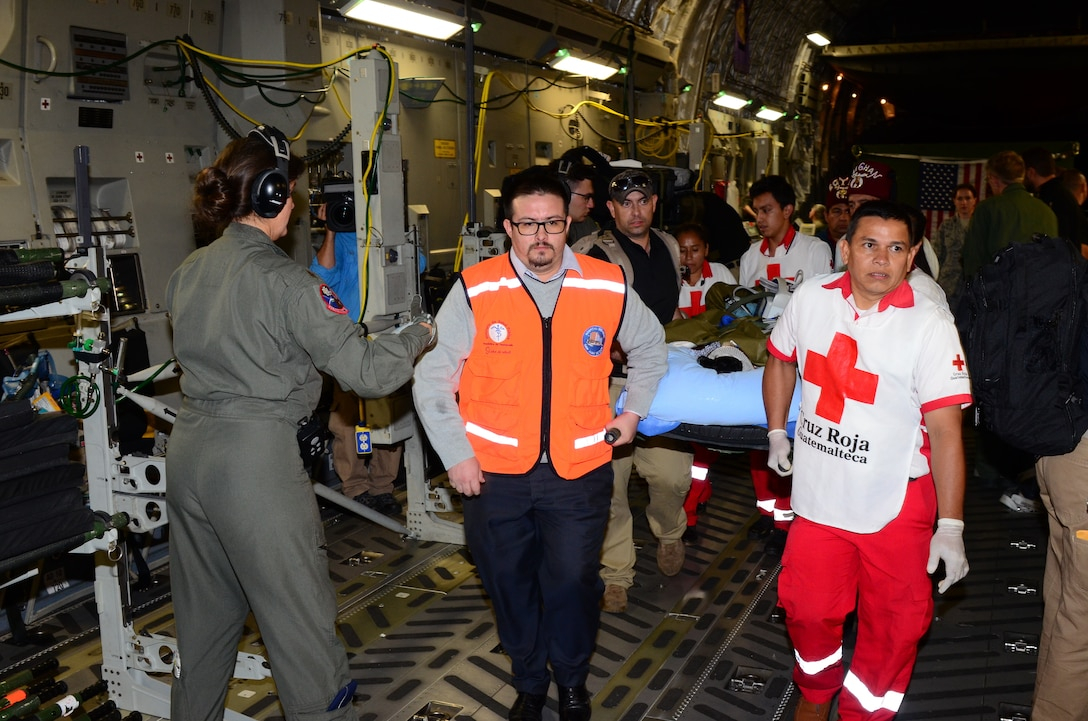 Guatemalan and United States military Fuego relief personnel load critically injured patients onto a 172d Airlift Wing C-17 Globemaster. The humanitarian airlift aeromedical evacuation mission was conducted at the direction of U.S. Southern Command to assist the government of Guatemala following the recent eruption of Fuego Volcano. (U.S. Air Force photo by Tech. Sgt. Edward Staton)