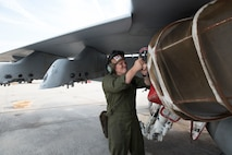Lance Cpl. Hunter Cauthron places a screen over the engine intake of an F/A-18 Hornet aboard Marine Corps Air Station Beaufort June 6.