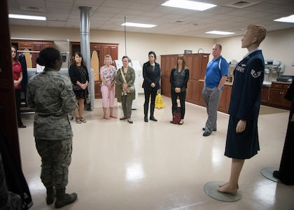 Volunteers listen to a brief in the uniform section of Air Force Mortuary Affairs Operations.