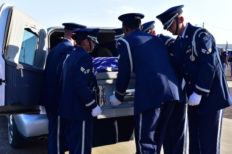 Airmen load a coffin onto the back of a hearse.