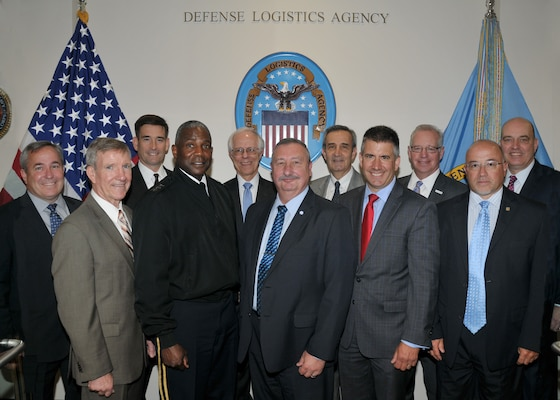 Group of industry leaders and DLA leaders pose before event.