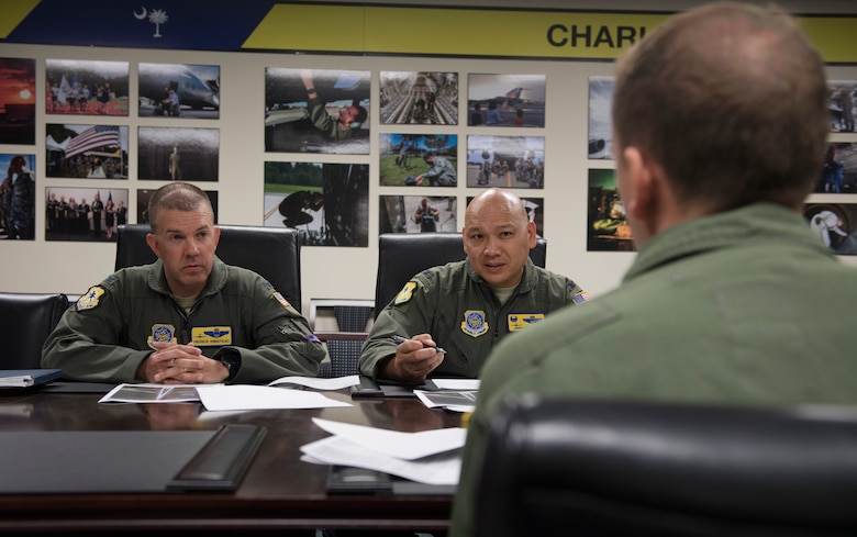 Col. Patrick Winstead, left, 437th Airlift Wing vice commander, and Col. Jimmy Canlas, middle, 437th Airlift Wing commander, discuss a proposal to enhance runway operations at North Auxiliary Airfield, North, S.C., with Maj. Ron Howard, 437th Operations Squadron assistant director of operations, during the Squadron Innovation Fund panel meeting June 4, 2018.