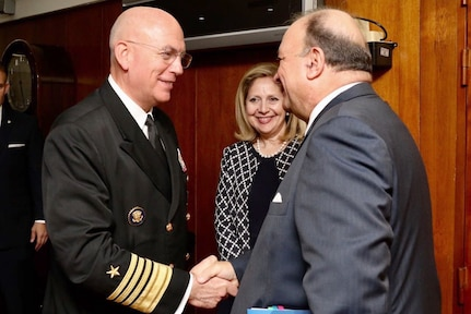 Navy Adm. Kurt W. Tidd shakes hands with Colombia's defense minister in a wood-paneled room.