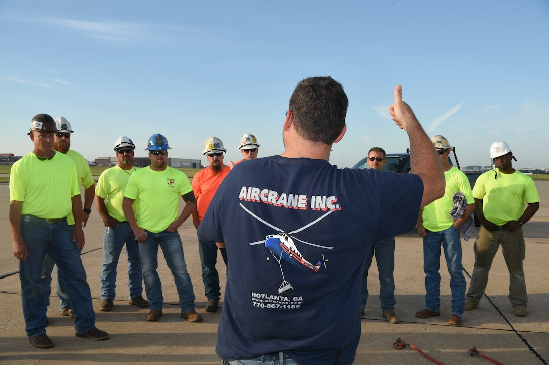 Jamey Culverson, a heavy-lift specialist with Aircrane Incorporated, briefs trademen from Matherly Mechanical contractors on safe operations under or near Aircrane's Sikorsky S-58T heavy-lift helicopter before the planned move of 57 heating units to the roof of building 3001 May 27, 2018, Tinker Air Force Base, Oklahoma.