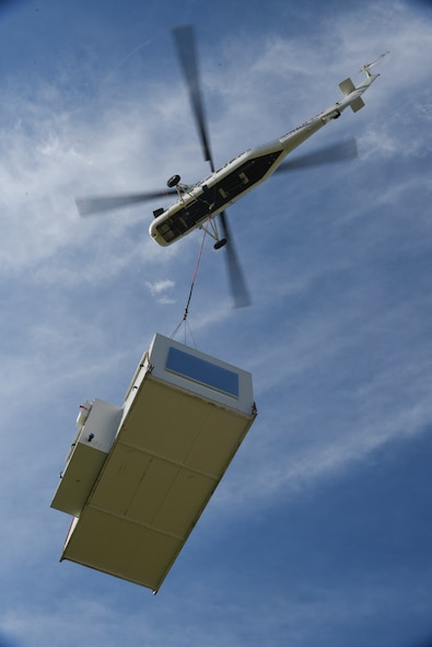 A Sikorsky S-58T heavy-lift helicopter from Aircrane Incorporated lifts a large heating unit May 27, 2018, Tinker Air Force Base, Oklahoma.