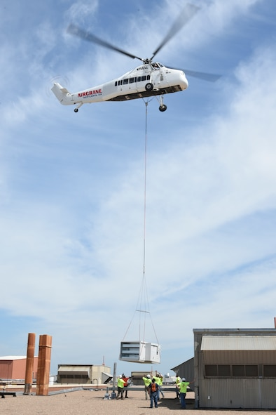 Tradesmen from Matherly Mechanical contractors look up as a large heating unit is lowered in to place by a Sikorsky S-58T heavy-lift helicopter from Aircrane Incorporated May 27, 2018, Tinker Air Force Base, Oklahoma.