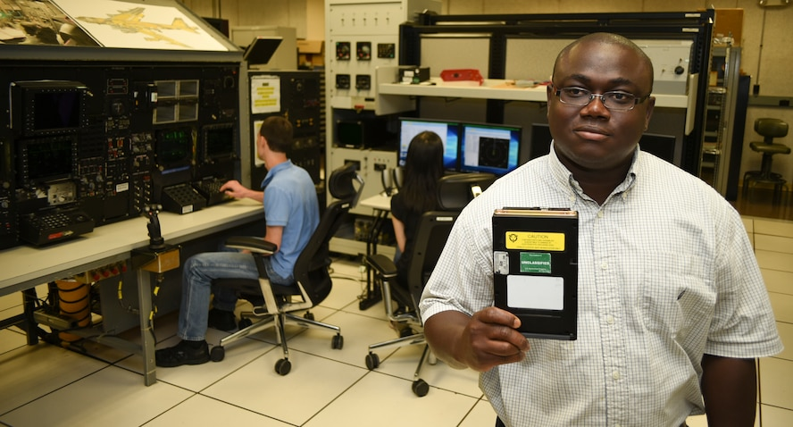 Emmanuel Koomson, 557th Software Maintenance Squadron lead test engineer holds a data transfer cartridge for the B-52H which contains the latest software upgrades developed by his team in the Mission Planning Environment section in the B-52 software test lab on May 29, 2018, Tinker Air Force Base, Oklahoma.