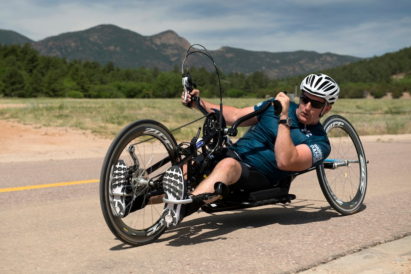 Navy Chief Petty Officer Mathew Parker turns a hand cycle along the 2018 DoD Warrior Games time trials competition course during the Department of Defense Warrior Games at the U.S. Air Force Academy in Colorado Springs, Colo.