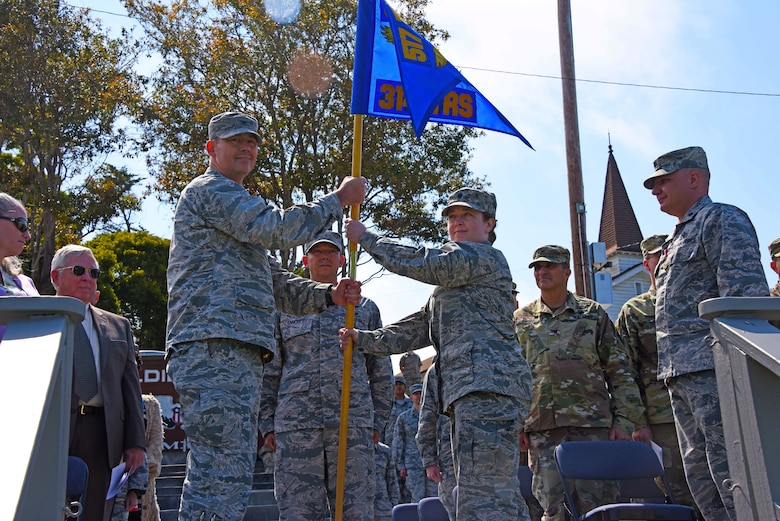 U.S. Air Force Col. Wiley Barnes, 517th Training Group Commander, passes the 314th Training Squadron guideon to Lt. Col. Jaclyn DeRoush, 314th TRS incoming commander, at the 314th TRS Change of Command at the Presidio of Monterey, California, June 6, 2018. The guideon signifies the passing of command from one commander to the next. (U.S. Army photo by Natela Cutter/Released)