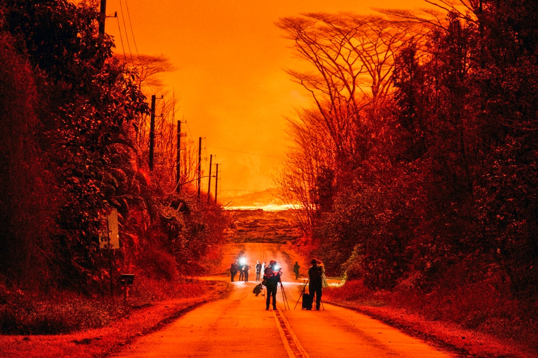 People with lights and equipment walk down a street against the backdrop of a fiery orange sky.