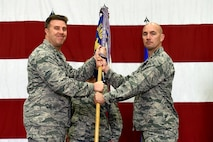 U.S. Air Force Maj. Timothy Liebold receives the 51st Munitions Squadron (MUNS) guidon from Col. Michael Hammond, 51st Maintenance Group commander, during a change of command ceremony at Osan Air Base, Republic of Korea, June 8, 2018.