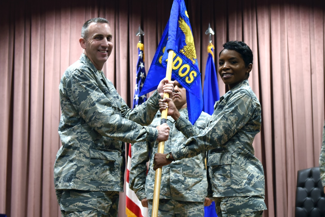 U.S. Air Force Col. Christopher Estridge, 39th Medical Group commander, passes the guidon to Lt. Col. Sarah Evans as she assumes command of the 39th Medical Operations Squadron, during a formal ceremony at Incirlik Air Base, Turkey, June 8, 2018.