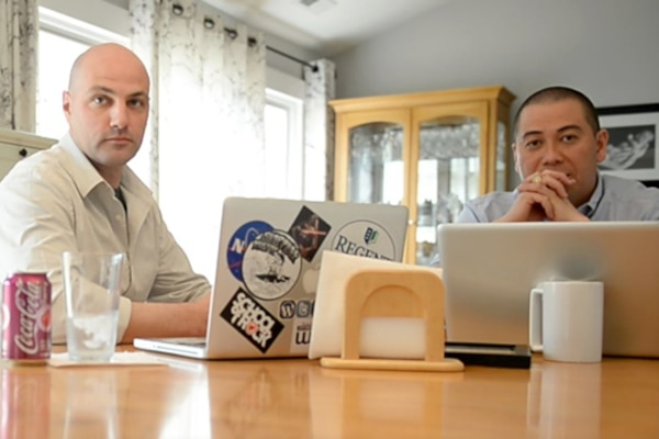 Two people sit at a home kitchen table with laptops.