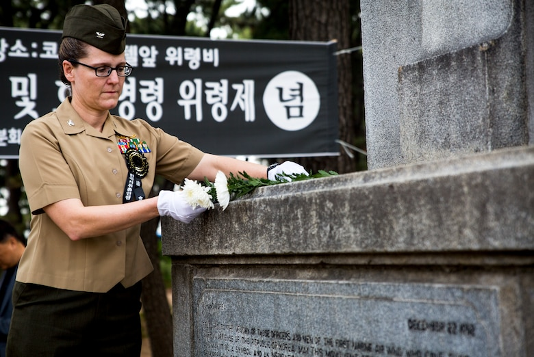 U.S. Marine Col. Maria McMillen places a flower on the 1st Marine Aircraft Wing Memorial Monument during a memorial ceremony at Pohang City Battle Monument and 1st MAW Memorial Monument in Pohang, South Korea, June 6, 2018. One at a time, each guest placed a flower on the memorial. McMillen, a Craig, Colorado native, is the G-5 assistance chief of staff with 1st MAW.
