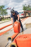 Firefighter and EMT rolls out water hoses during a routine pressure testing