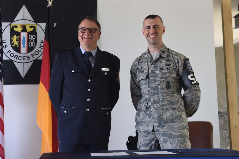 Ingolf Hubert, left, Polizei head of department of education and training, and U.S. Air Force Lt. Col. Jason Sleger, 569th U.S. Forces Police Squadron commander, pose for a photo after signing a memorandum of agreement on Kapaun Air Station, Germany, June, 6, 2018. The 569th USFPS and Polizei partnership demonstrates a model of American and German partnership.