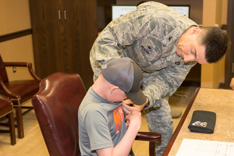 Mason Ogle receives an Air Force Meteorology occupational badge from Col. Thomas Blazek, 1st Weather Group commander, May 11, 2018, at Offutt Air Force Base, Nebraska. Mason, who is battling cancer, visited the 557th Weather Wing to learn more about meteorology and Air Force Weather. (U.S. Air Force photo by Paul Shirk)