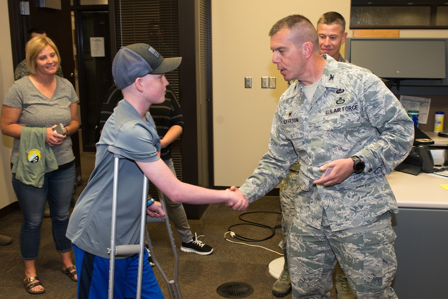 Mason Ogle is coined by Col. Steven Dickerson,  557th Weather Wing commander, May 11, 2018, at Offutt Air Force Base, Nebraska. Mason, who is battling cancer, wants to pursue a career in meteorology. (U.S. Air Force photo by Paul Shirk)