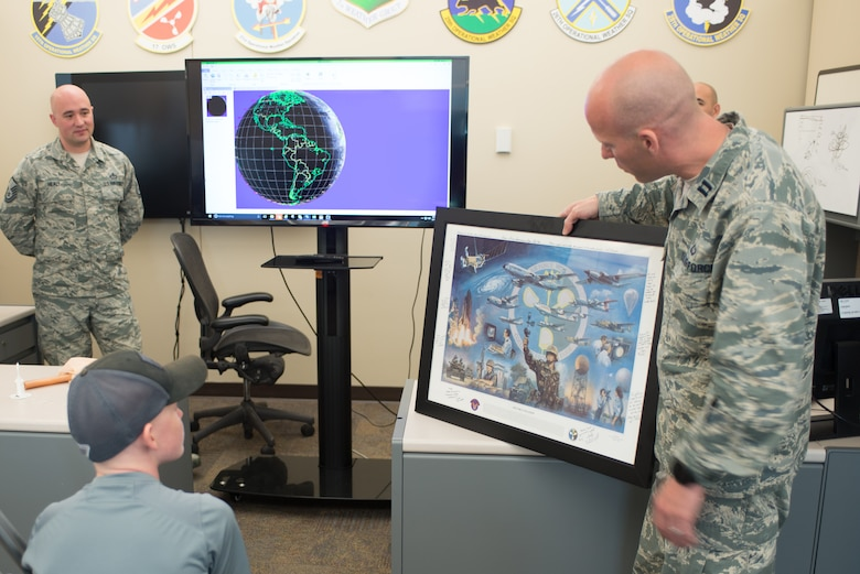 Capt. Dan Alexander, 1st Weather Group executive officer, presents Mason Ogle with a signed lithograph donated by members of the 1st Weather Group May 11, 2018, at Offutt Air Force Base, Nebraska. Mason, who is battling cancer, learned about weather radar and how weather observations are made  during his visit. (U.S. Air Force photo by Paul Shirk)