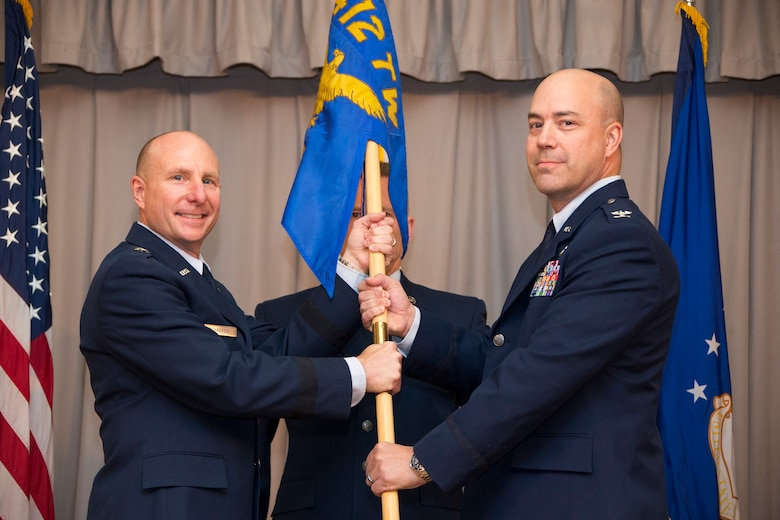Brig. Gen. Carl Schaefer, 412th Test Wing commander (left), hands Col. Jeffry Hollman, the 412th Mission Support Group guidon during an assumption of command ceremony held June 4 at Club Muroc. (U.S. Air Force photo by Christopher Okula)