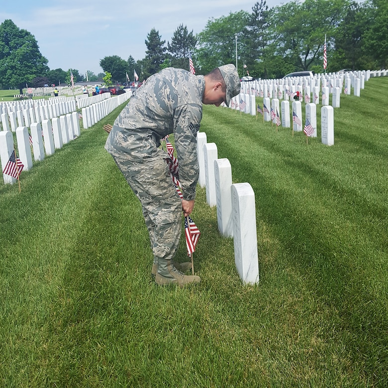 Senior Airman Millar, assigned to the 14th Intelligence Squadron, 655th Intelligence, Surveillance and Reconnaissance Group, plants an American flag on the grave of a servicemember during a Memorial Day service at the Dayton Veteran's Cemetery, Dayton, Ohio, May 28, 2018.
