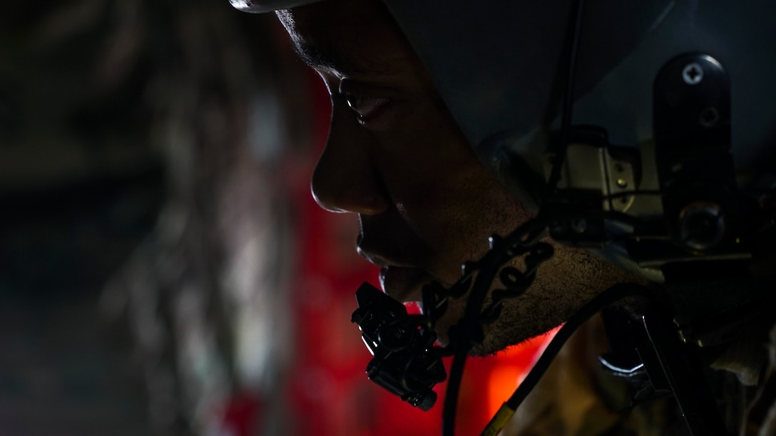 A C-130H Hercules loadmaster assigned to the 746th Expeditionary Airlift Squadron, Al Udeid Air Base, Qatar, listens to pilot instructions prior to a combat airdrop over an undisclosed location June 3, 2018. This was the first combat air drop for the loadmaster who is deployed from the 908th Airlift Wing, Maxwell Air Force Base, Ala. (U.S. Air Force photo by Master Sgt. Burt Traynor)
