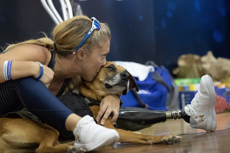Retired Senior Airman Heather Carter takes a break with service dog Rocky after competing in sitting volleyball at the Department of Defense Warrior Games 2018.  Warrior Games is a Paralympic style competition where wounded warriors compete in 11 different adaptive sporting events. Competition this year started June 1 and runs through June 9.  (U.S. Air Force photo by Master Sergeant David Long)