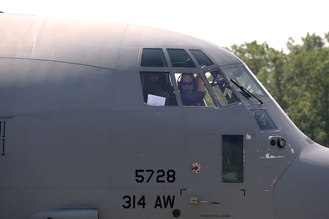 A man wearing sunglasses looks out the front of the windows in a C130J.