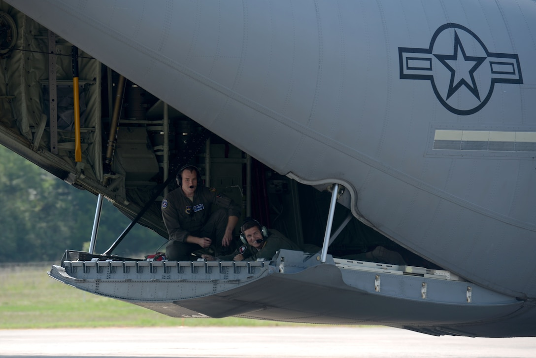 Two men wearing green flight suits sit on the back of an open C130J ramp.