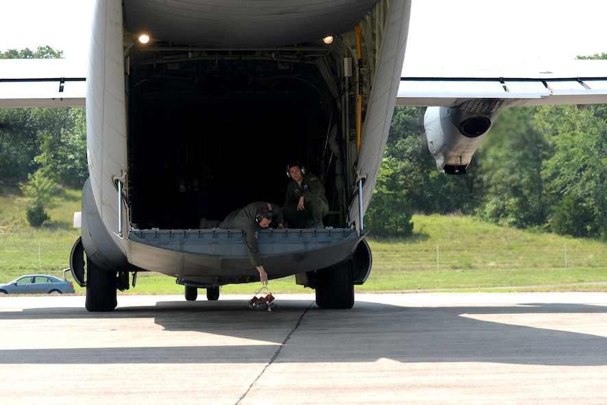 Two men sit on the back of an open ramp on a C130J while one of them drops a sandbag onto the ground.
