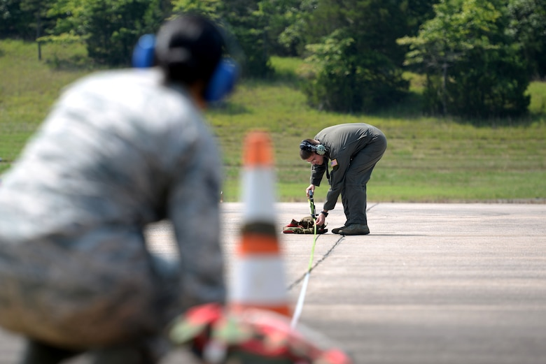 A woman wearing the Airman Battle Uniform with blue ear covers holding down a measuring tape at an orange cone while a man wearing a green flight suit pulls the other end of the measuring tape to a sand bag.