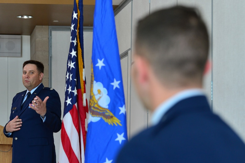 Lt. Col. Daniel Finkelstein, presiding officer of Maj. Phillip's promotion, talks about the accomplishments of Maj. Phillip, 732nd Operations Group chief of intelligence, during his promotion ceremony March 31, 2018, in Las Vegas. Phillip received a Reserve Officers' Training Corps scholarship and commissioned upon graduation in 2008. (U.S. Air Force photo by Airman 1st Class Haley Stevens)