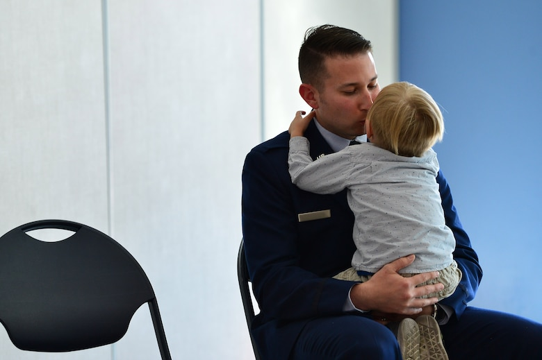 Maj. Phillip, 732nd Operations Group chief of intelligence, gives his son a kiss during his promotion ceremony March 31, 2018, in Las Vegas. Many of Phillip's family members travelled from all over the nation to celebrate his promotion. (U.S. Air Force photo by Airman 1st Class Haley Stevens)