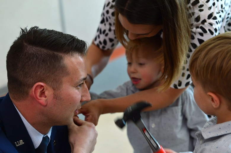 Maj. Phillip, 732nd Operations Group chief of intelligence, gets his rank pinned on by his wife and children during his promotion ceremony March 31, 2018, in Las Vegas. Phillip was surrounded by family and friends who came to celebrate his promotion to major. (U.S. Air Force photo by Airman 1st Class Haley Stevens)