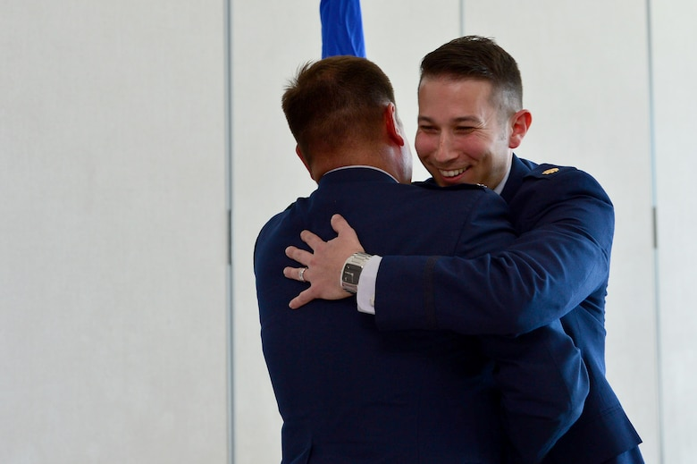 Maj. Phillip, 732nd Operations Group chief of intelligence, hugs Lt. Col. Daniel Finkelstein, presiding officer of Maj. Phillip's promotion, after his oath of office March 31, 2018, in Las Vegas. Phillip has served in the U.S. Air Force for 10 years and is proud to continue his family's legacy as a third generation Airman. (U.S. Air Force photo by Airman 1st Class Haley Stevens)