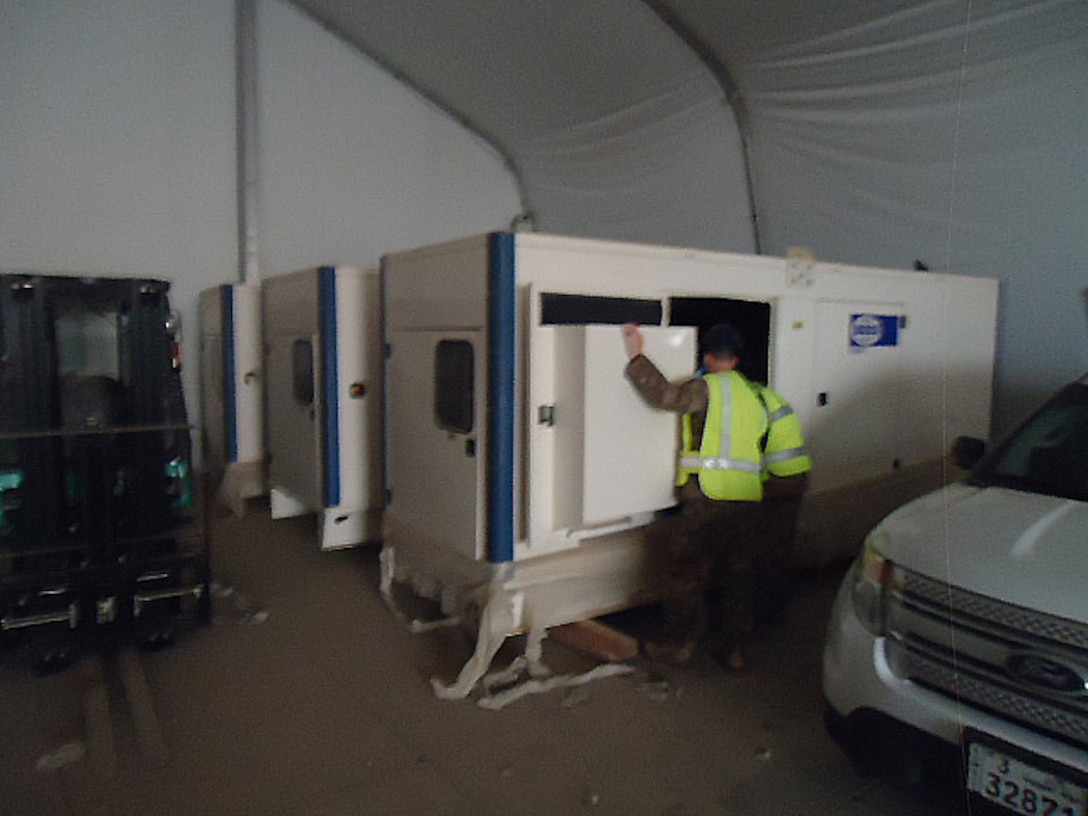 Engineers from the host installation and DLA Disposition Services Installation Operations inspect generators before they are put into service to electrify large area maintenance shelters.